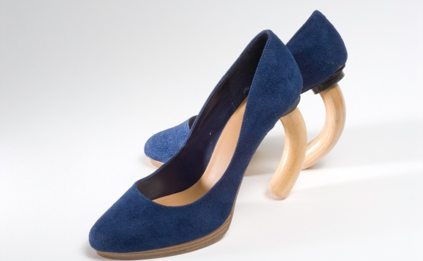 Pair of blue high heel shoes where the actual heels have been replaced by the curved handle of a wooden cane.